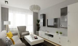 """Sofa jasno-szara. Meble w kolorze białym. Dodatkowo półki """"słupki"""" z kolorze czarnym"""